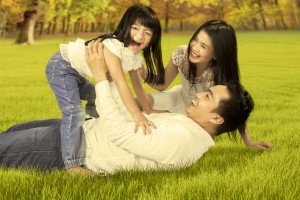 45124962 - portrait of happy asian family enjoying holiday by playing together on the autumn park